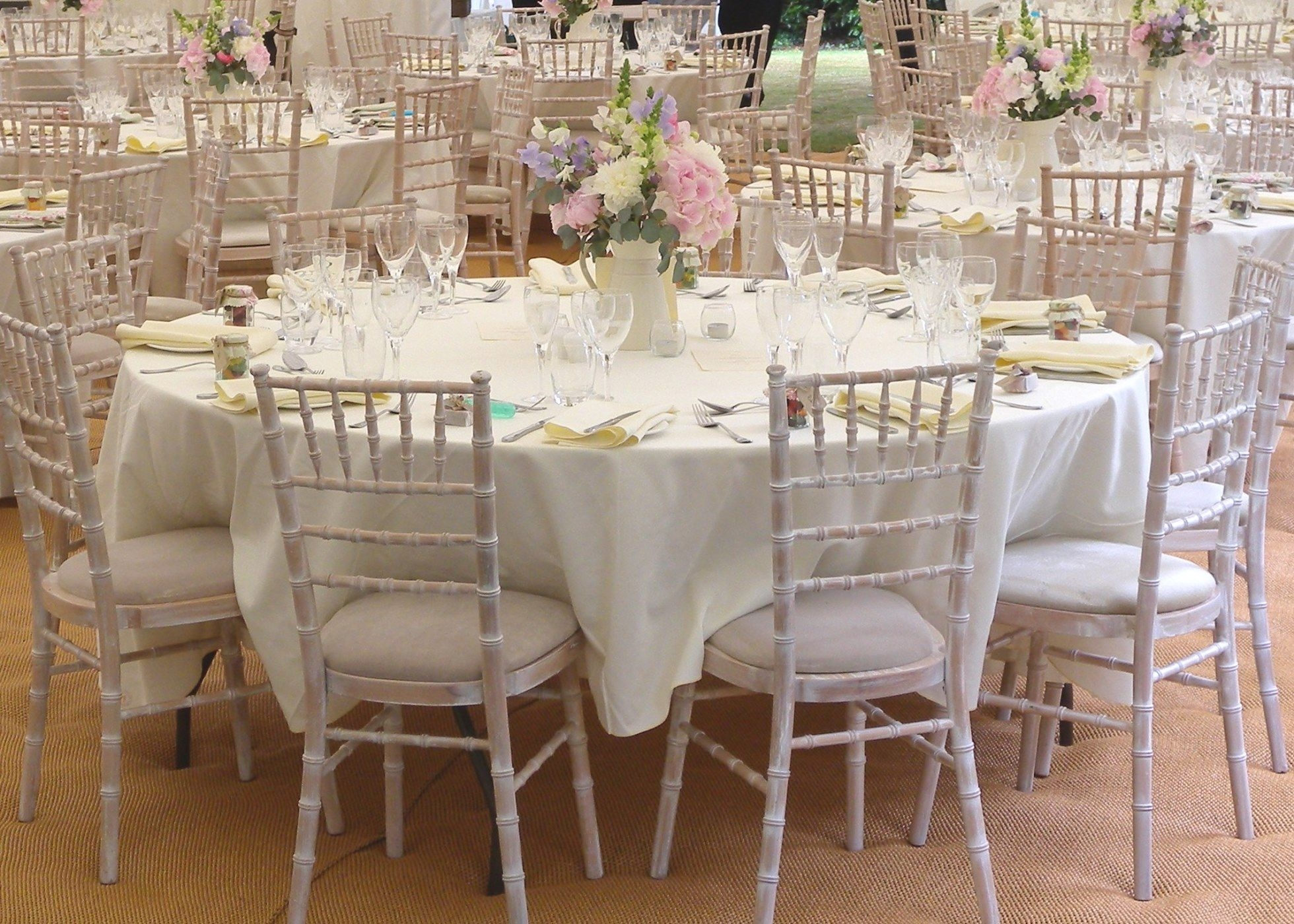 Interior shot of Wedding marquee table setting with Limewash Chiavari chairs and table centres with sweet pea flowers