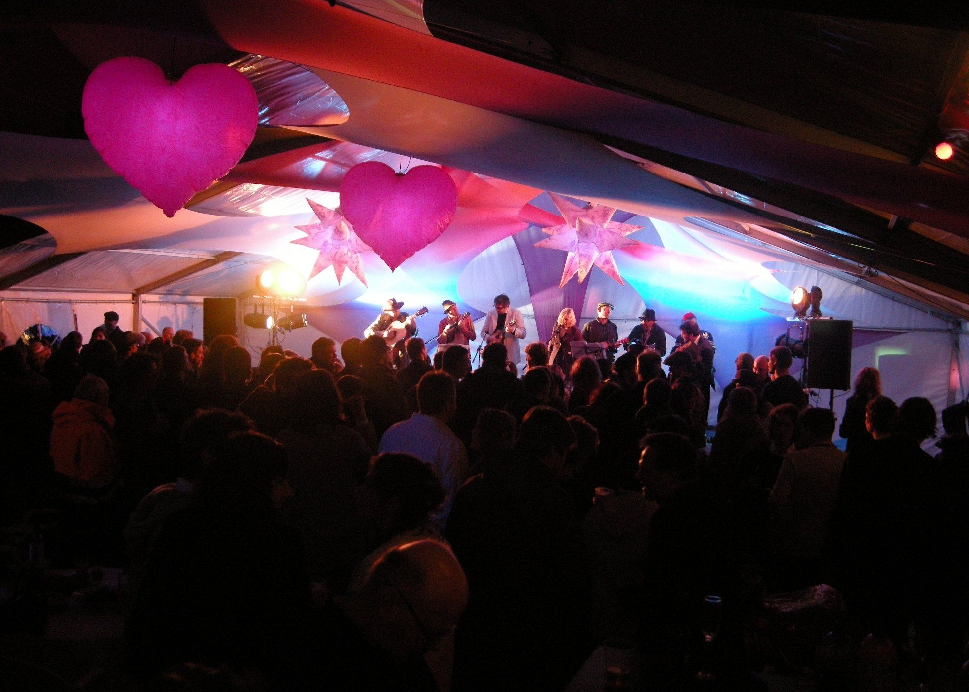 Inside of marquee at night with crowd watching Ukelele band on stage, inflatables & stretch lycra decor