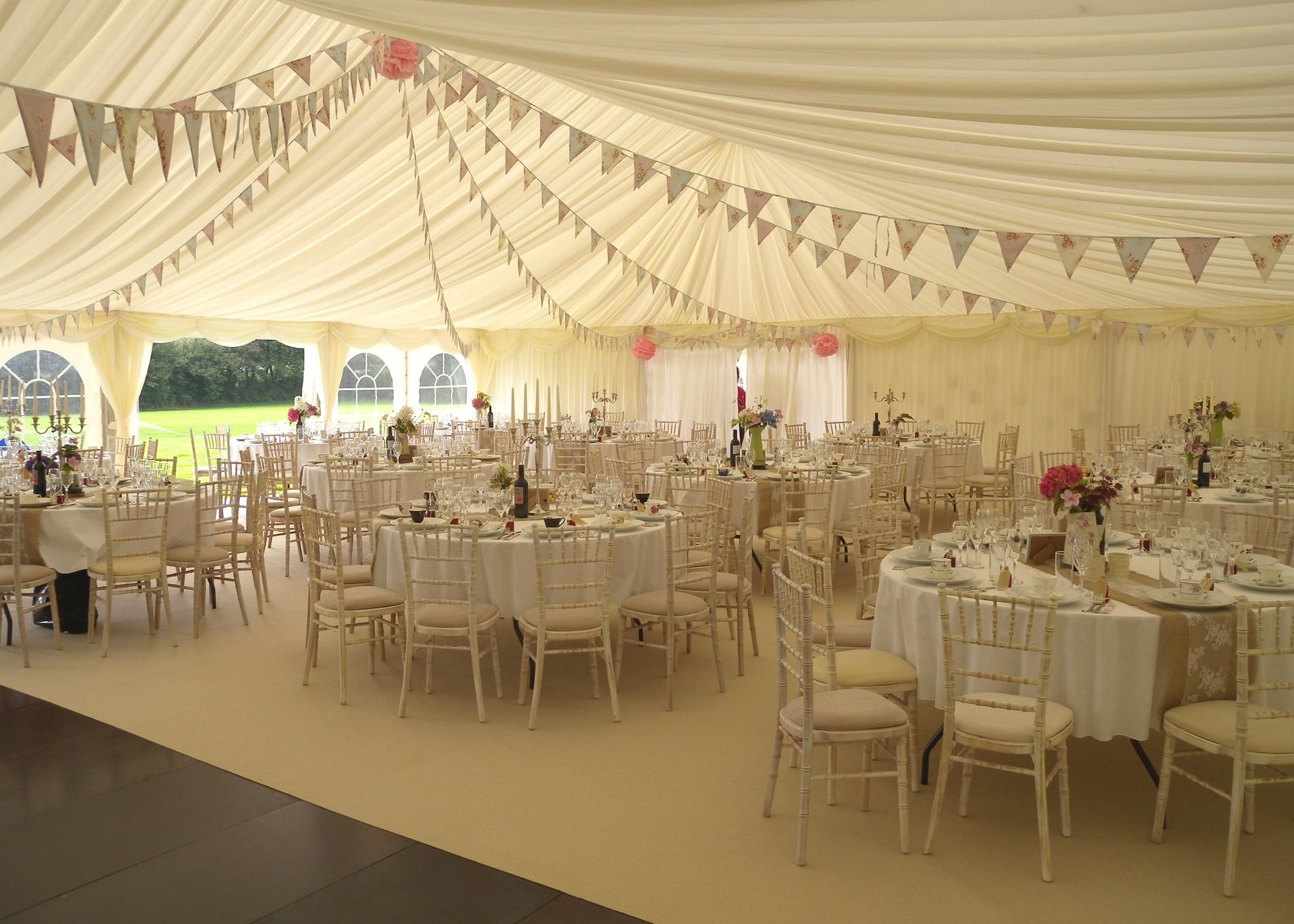 Wedding Marquee beautiful interior featuring bunting, candelabras, wooden flooring and carpet