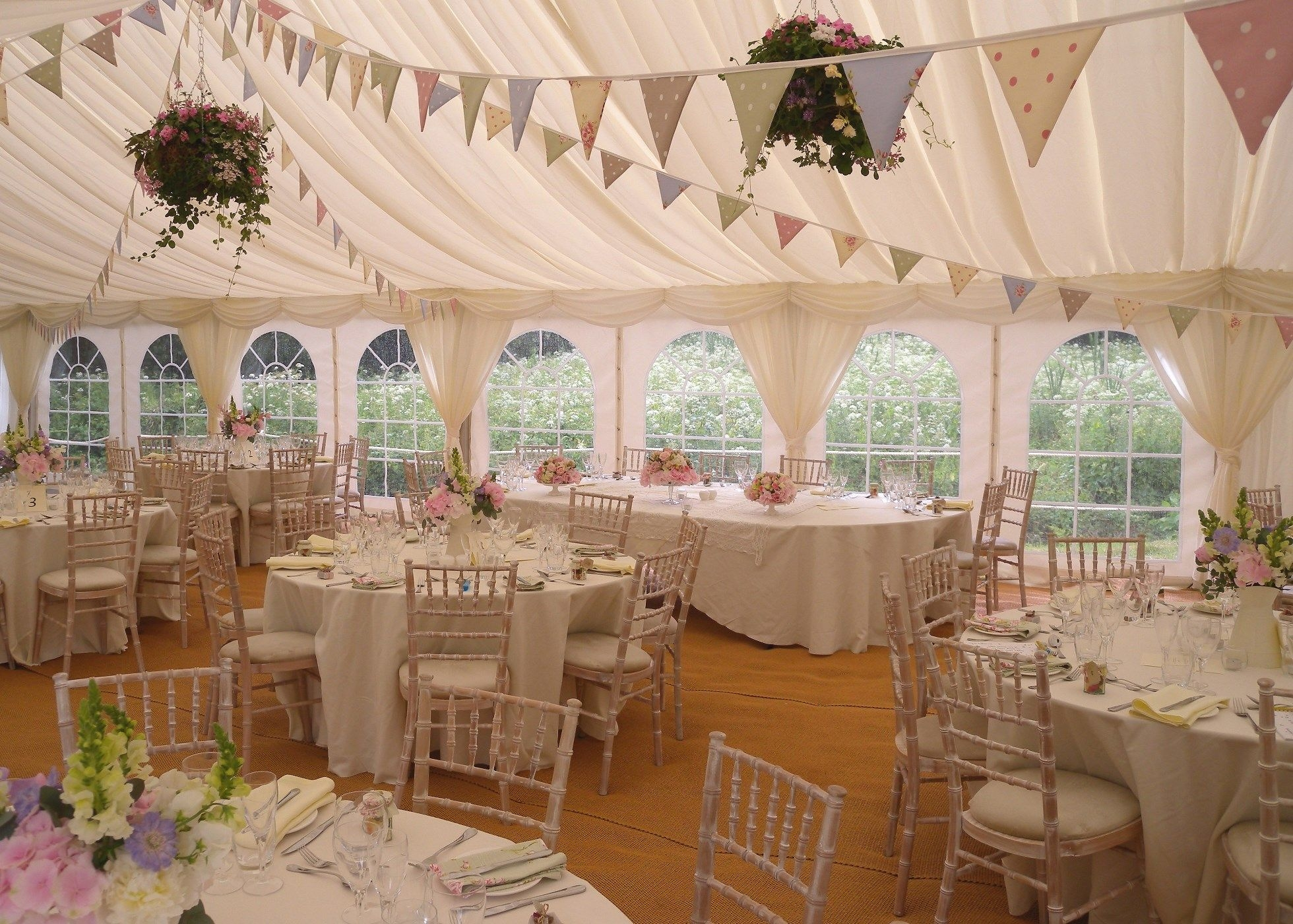 Interior photo of wedding marquee with bunting and hanging baskets