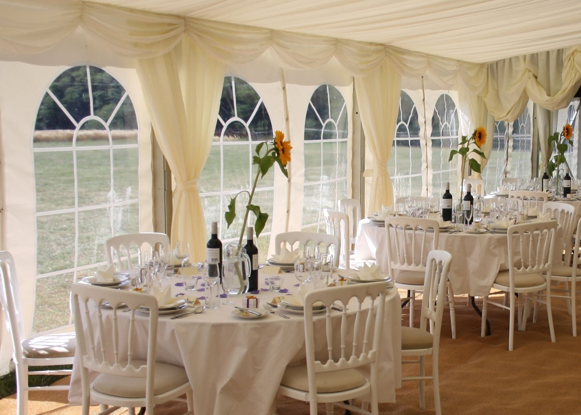 interior view of wedding marquee with sunflower table centres and white cheltenham chairs
