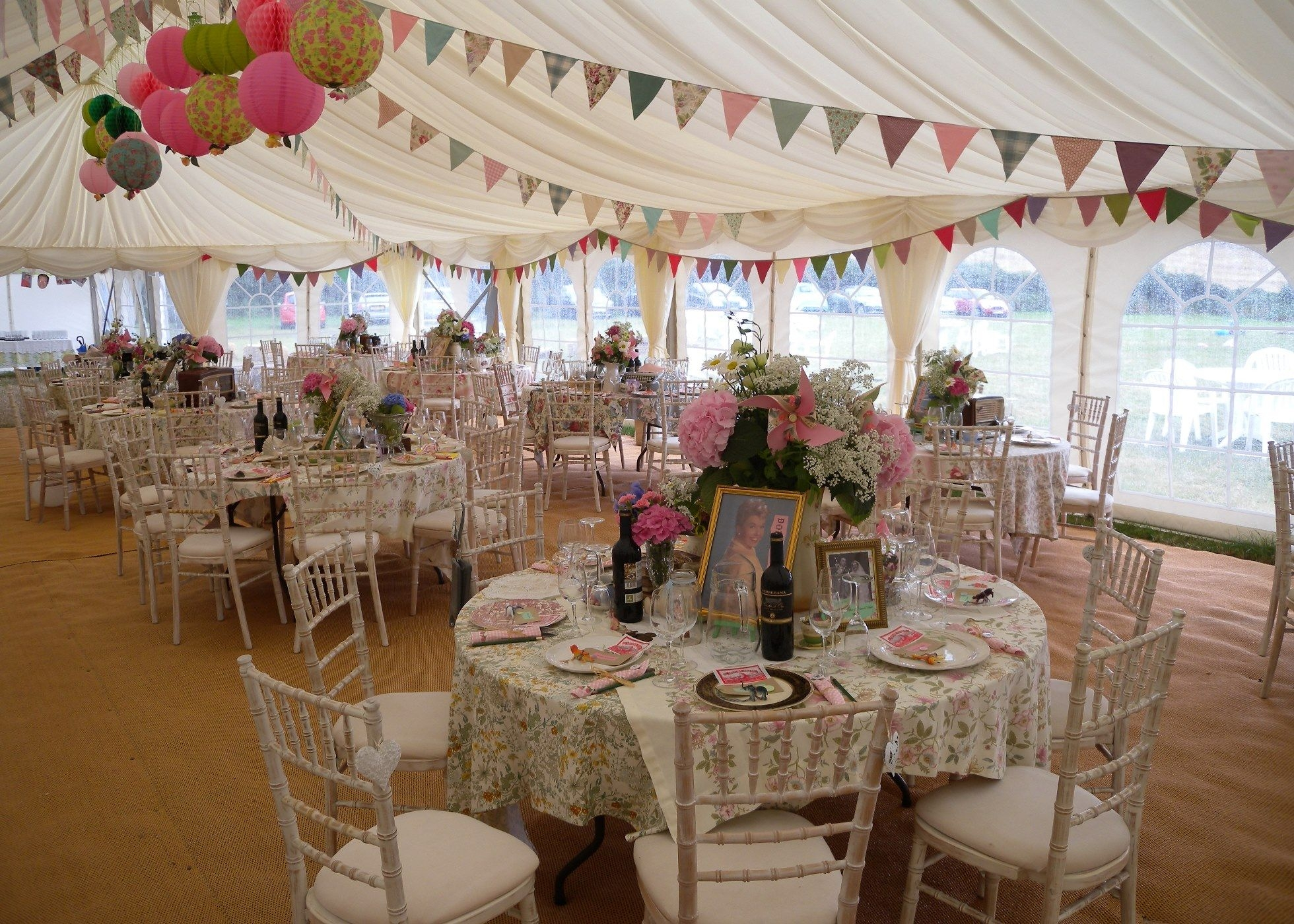 Wedding Marquee interior with vintage, 1950s style table settings, bunting and paper lanterns